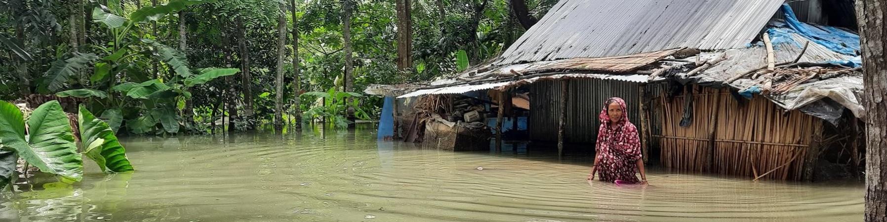 Una donna vicino alla sua capanna è immersa fino alla pancia nell acqua di un inondazione