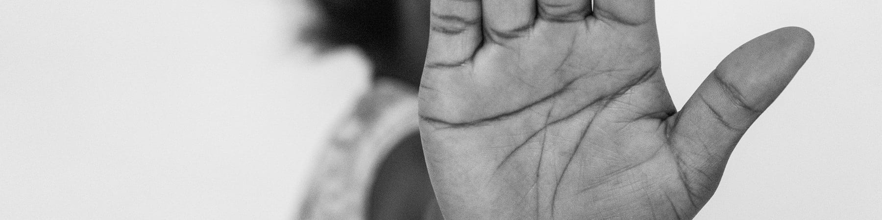 In primo piano la mano aperta in segno di stop di una ragazza nigeriana. Dietro la mano si intuisce un profilo di donna