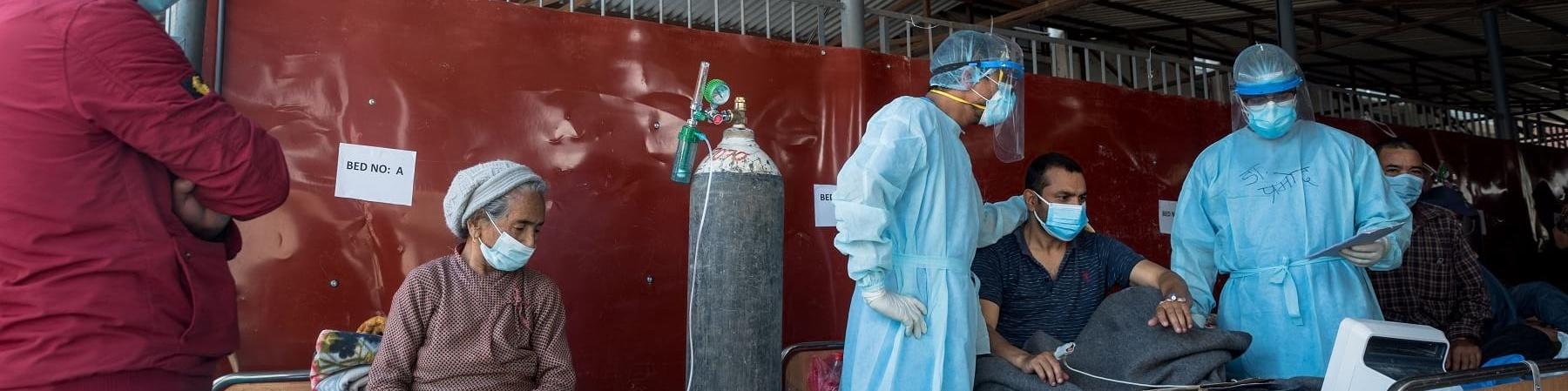 Stanza di ospedale in Nepal in cui si trovano due pazienti seduti sul letto e la mascherina e alcuni operatori vicino a loro.