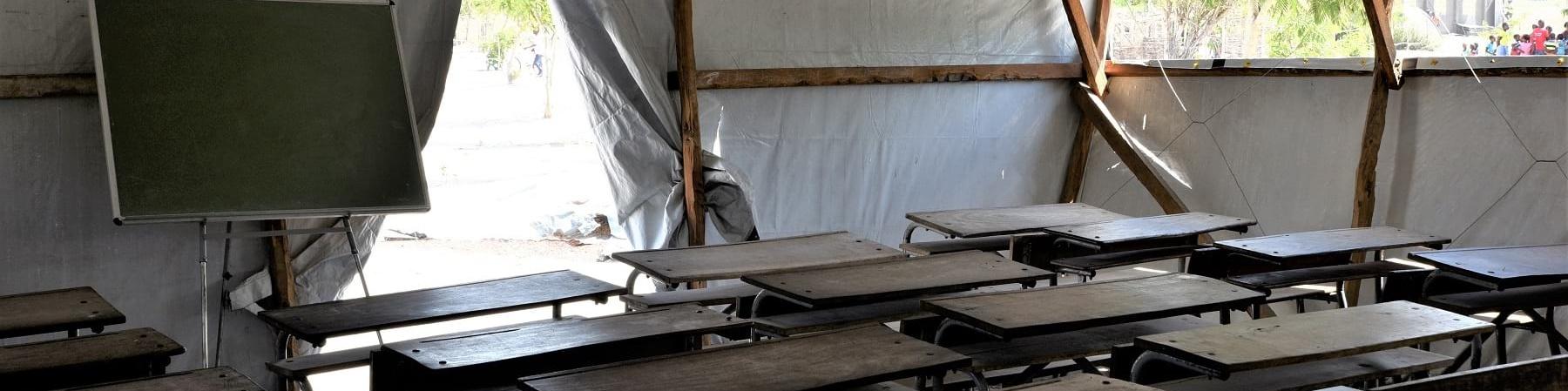 Aula con banchi di scuola e lavagna allestita in un tendone