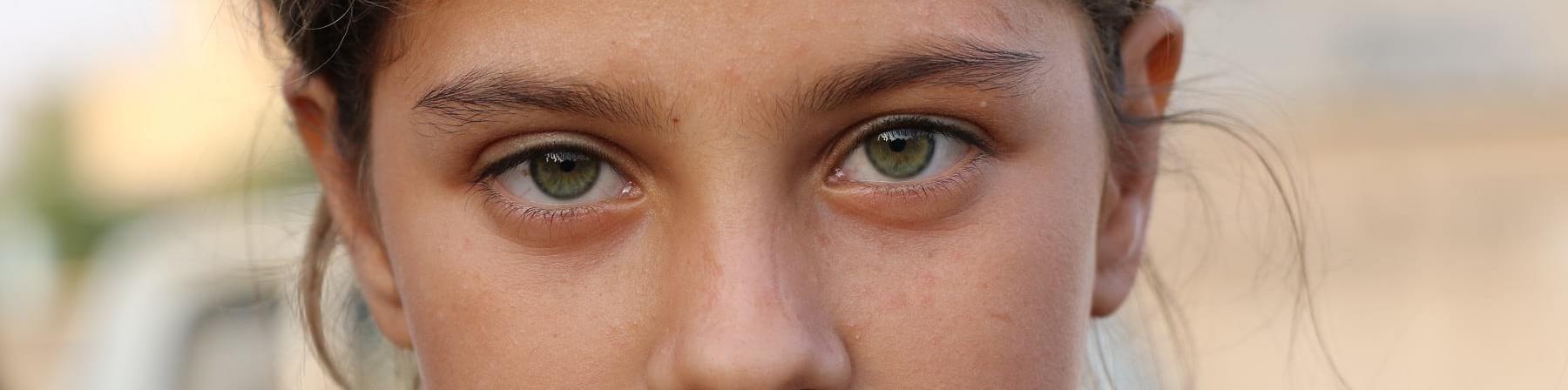primo piano di una bambina bionda con capelli legati e occhi verdi