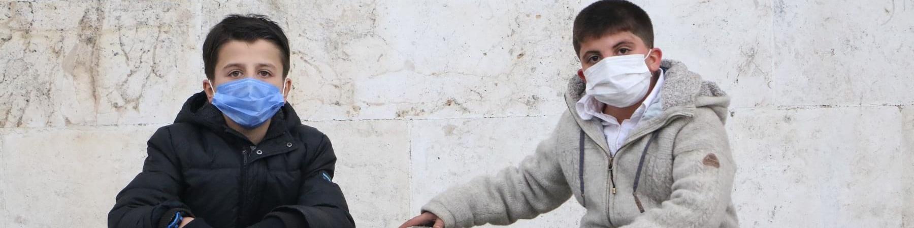 Due bambini siriani di 10 anni indossano la mascherina, un cappotto e dei jeans e sono seduti uno a fianco all altro su un gradino. Uno dei due tiene il braccio allungato lateralmente con la mano posata su un pallone, poggiato anch esso sul gradino.