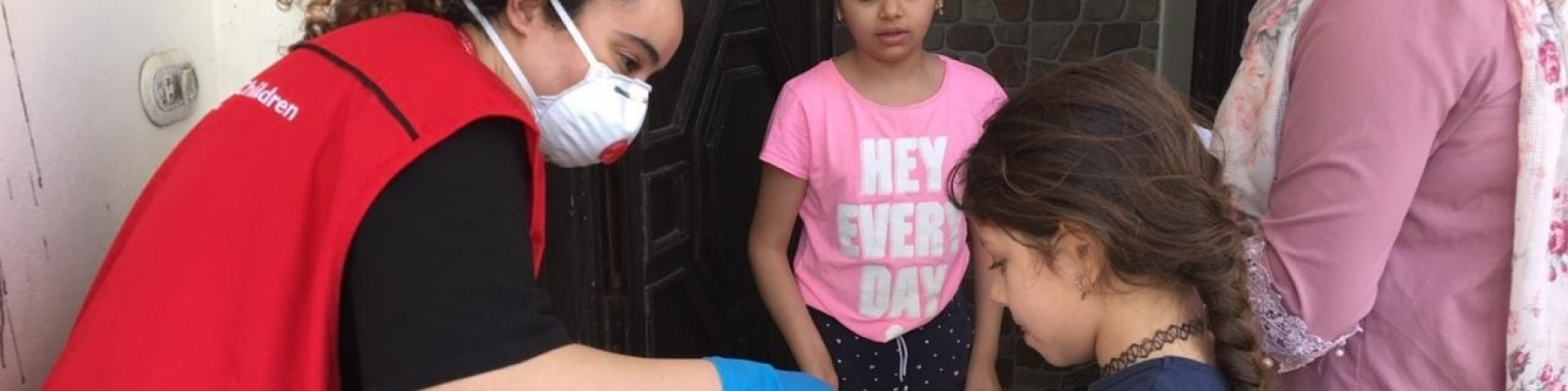 Operatrice save the children di spalle distribuisce kit scolastici a bambini libanesi
