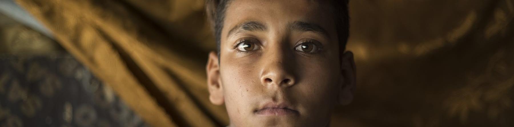 Primo piano bambino siriano moro guarda in camera