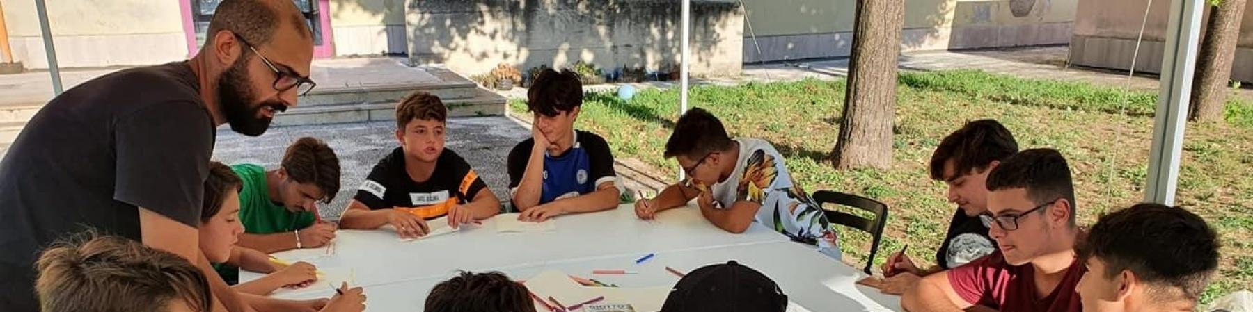 Studenti intorno a una tavola rotonda scrivono e studiano, un adulto li supervisiona