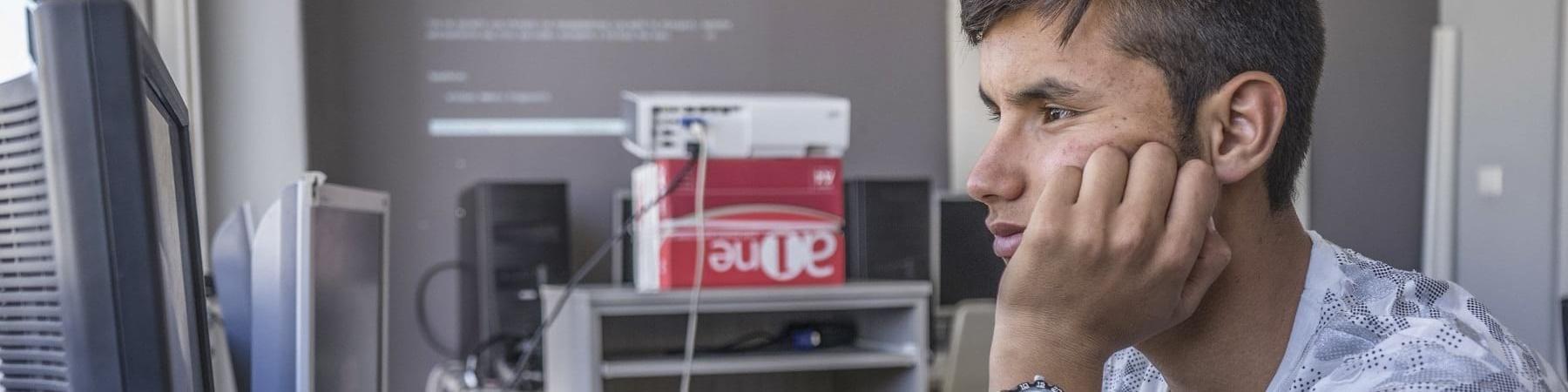Adolescente sta seduto davanti al computer