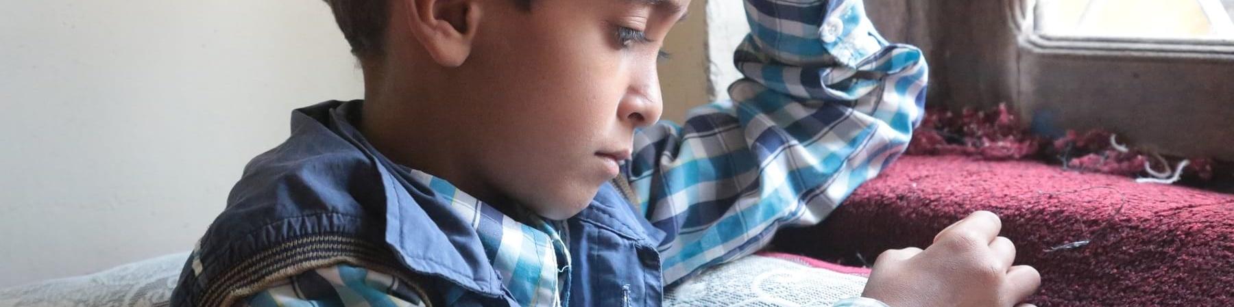Bambino yemenita seduto di profilo vicino a una finestra guarda verso il basso