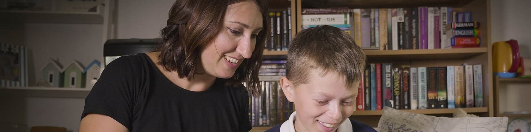Una mamma e suo figlio leggono insieme un libro seduto sul divano di casa