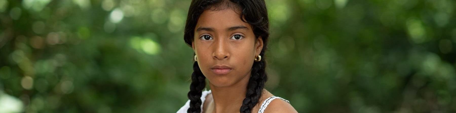 mezzo busto di una ragazzina mora con due treccine e maglietta bianca