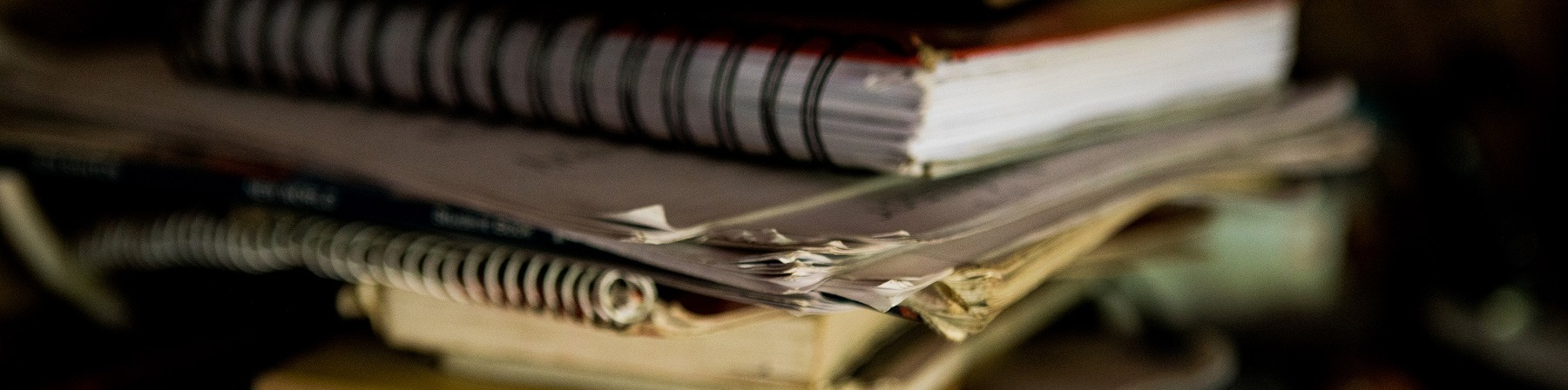 Pila di libri e quaderni su un tavolo.