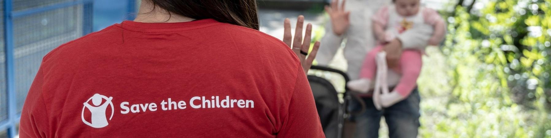 operatrice di save the children di spalle che saluta una mamma con un bimbo in braccio