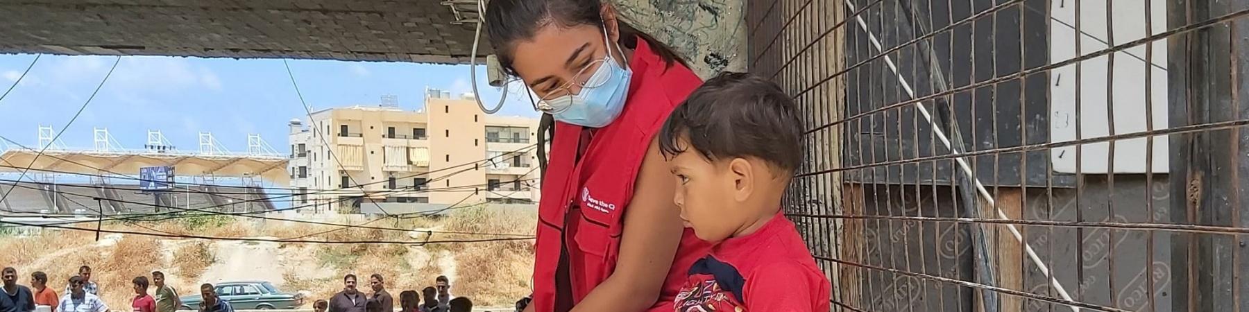 Operatrice Save the Children seduta su un muretto insieme a un bambino accanto a lei