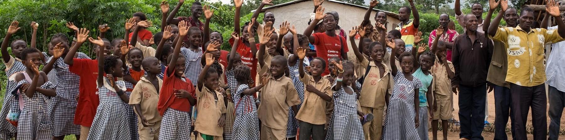 Comunita del cacao Ivoriana di bambini e adulti posa per una foto di gruppo davanti ad alcune case del villaggio