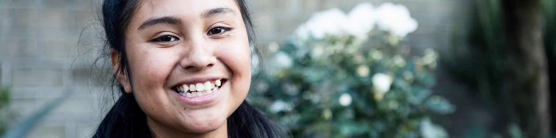 Mezzo busto di ragazza messicana sorridente con codine che indossa maglietta a righe bianche e nere