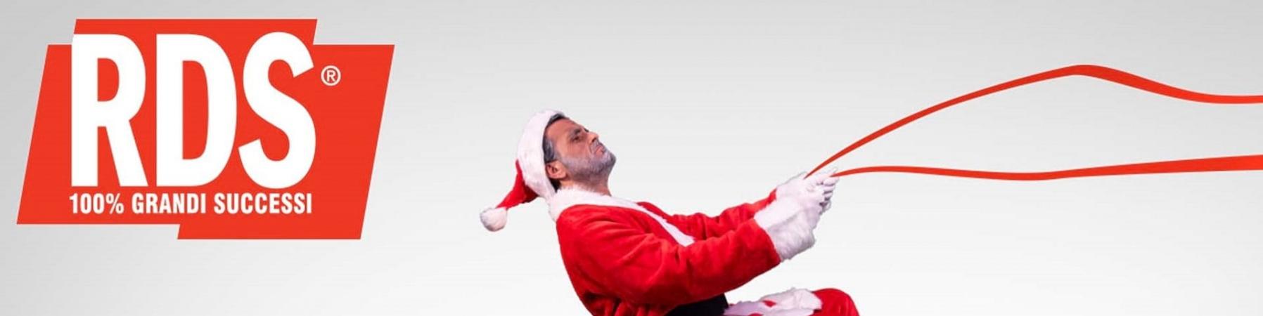 Un uomo vestito da Babbo Natale è seduto sul coperchio di un pacco regalo che gli fa da slitta