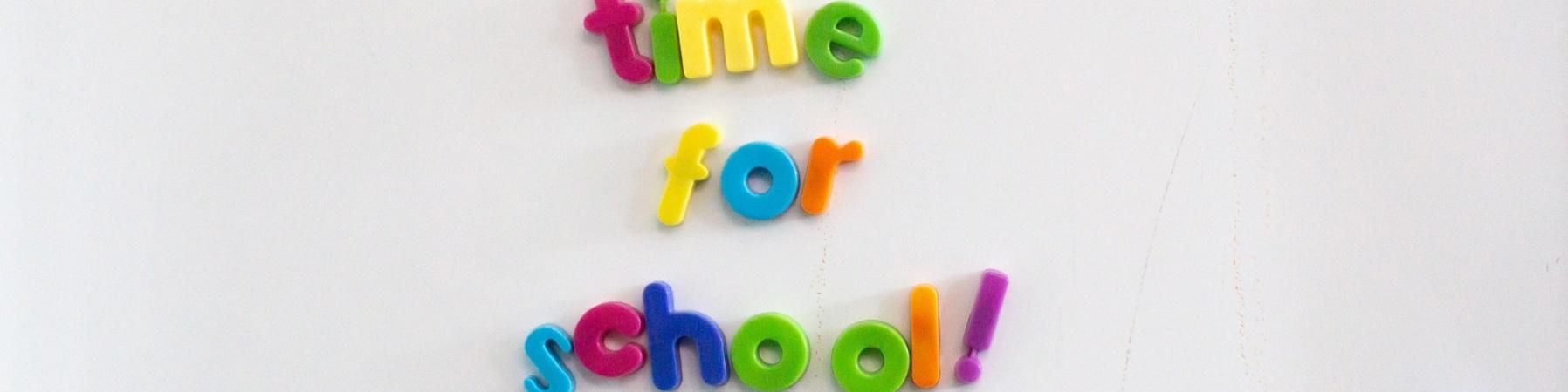 lavagna magnetica bianca con lettere colorate in basso a destra e in centro le lettere formano la scritta time for school