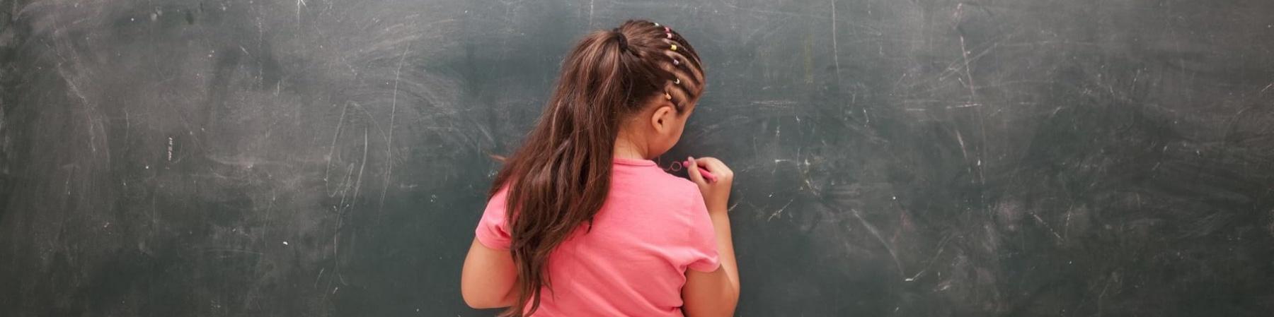 Bambina di spalle con maglietta rosa scrive alla lavagna
