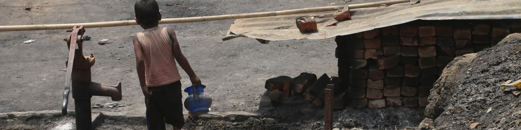 Un bambino di spalle con canottiera rossa e pantaloncini neri cammina a piedi scalzi tra le macerie di un incendio portando in mano un vaso
