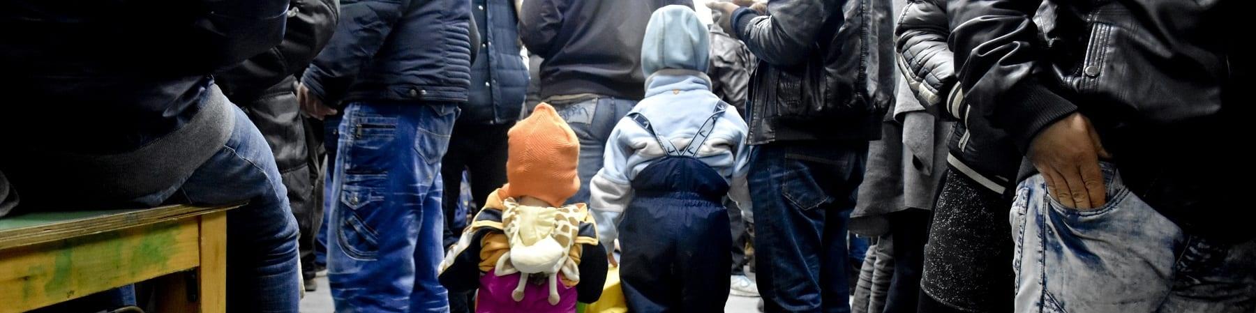 Due bambini molto piccoli di spalle sono in un ambiente chiuso molto affollato di cui si vedono soltanto le gambe e i piedi.