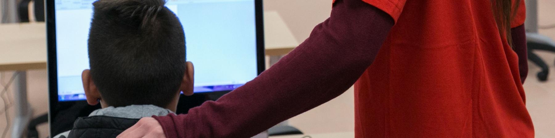 operatrice-mano-sulla-spalla-di-un-bambino-di-spalle-al-computer