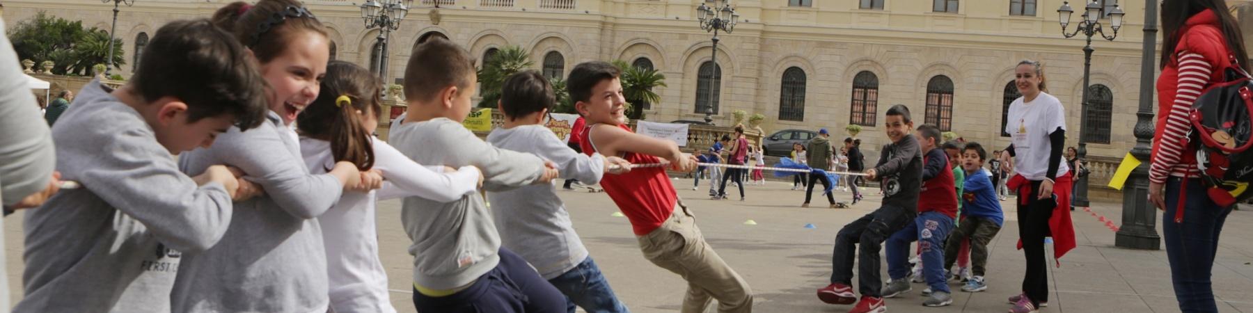 ragazzi giocano a tiro alla fune in piazza