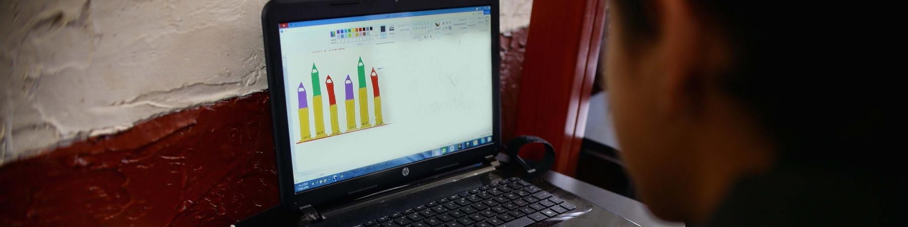 Bambino di spalle scrive vicino a un computer portatile sulla scrivania