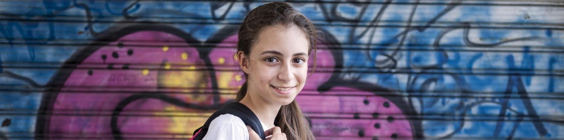 bambina con maglietta bianca e zaino viola sorride davanti a un murales