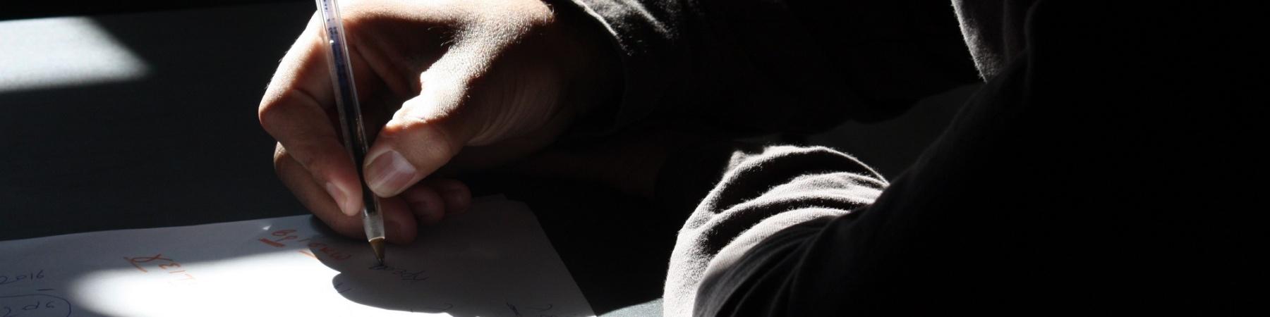 studente al banco di scuola scrive su un foglio