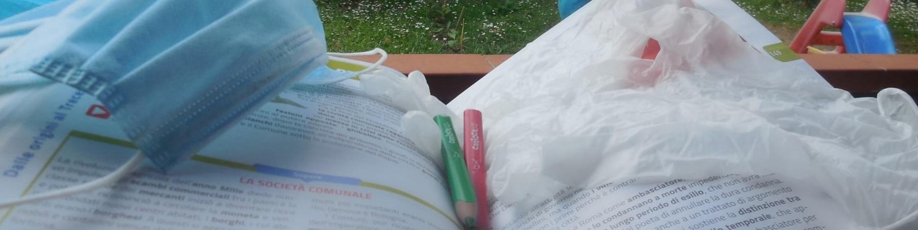 Mascherina, guanti e matite sopra un libro scolastico aperto. Sullo sfondo un giardino