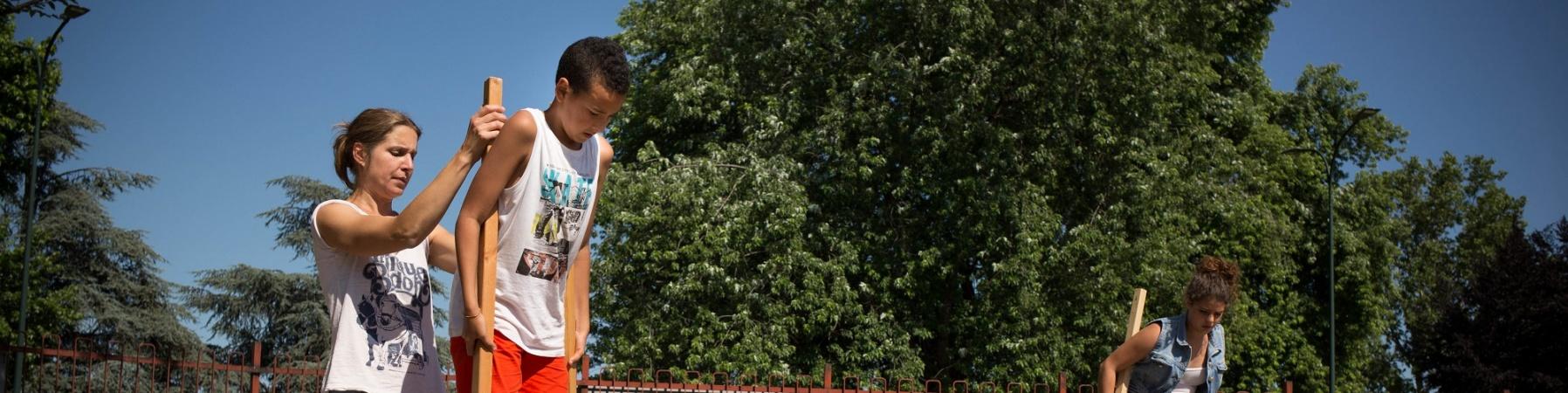 ragaza aiuta un bambino a stare sui trampoli in un parchetto e vicino un altra bambina è già sui trampoli