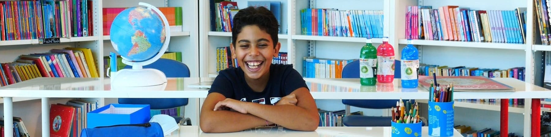 bambino seduto a scrivania con libri e penne sorride