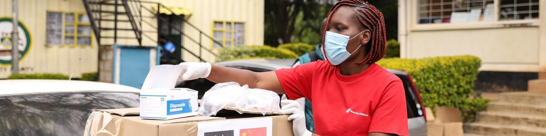operatrice keniana di save the children con treccine e capelli rossi indossa la mascherina e sta in piedi di profilo per prendere alcuni oggetti da una scatola poggiata su un piano davanti a lei. La ragazza indossa la maglietta rossa di Save the Children