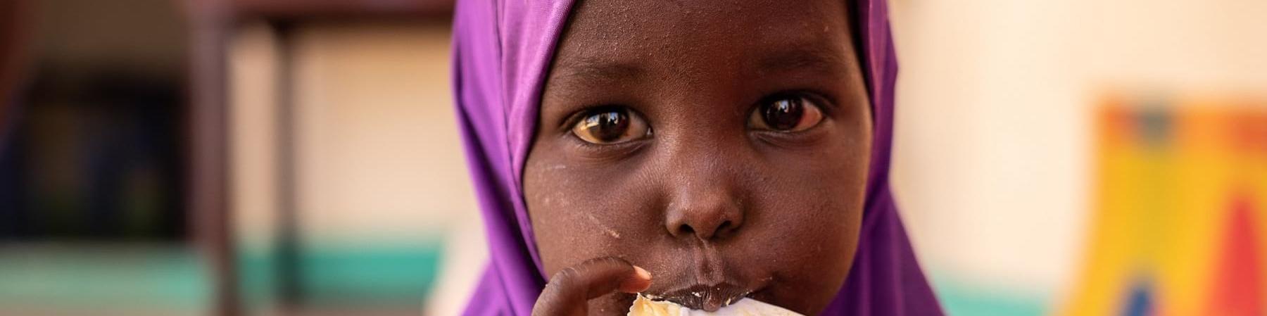 Bambina somala di pochi anni con chador viola in testa mangia una con le mani da una bustina di plumpynat