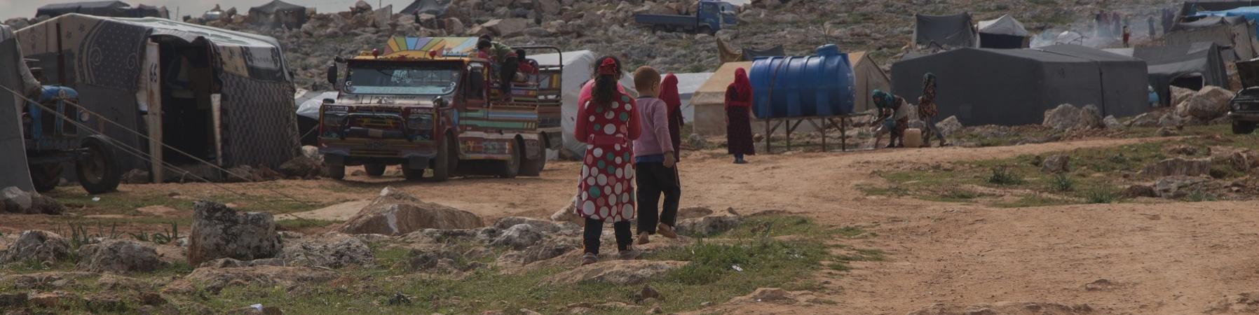 bambini di spalle in lontananza sullo sfondo di un accampamento di fortuna nel nord ovest della Siria