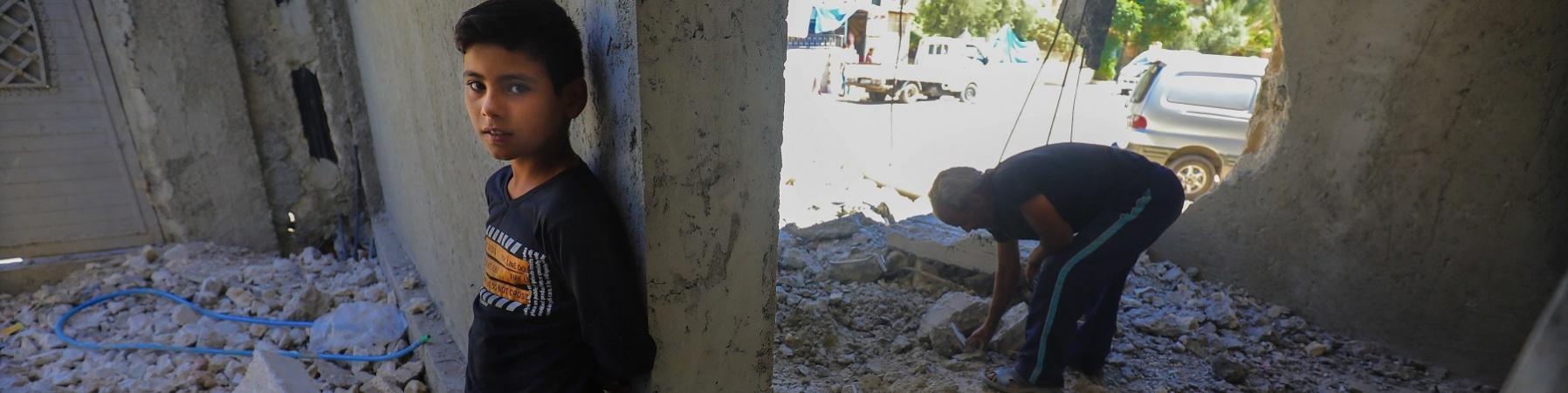 Un bambino è appoggiato con la schiena a un muro dentro un edificio distrutto e in mezzo alle macerie