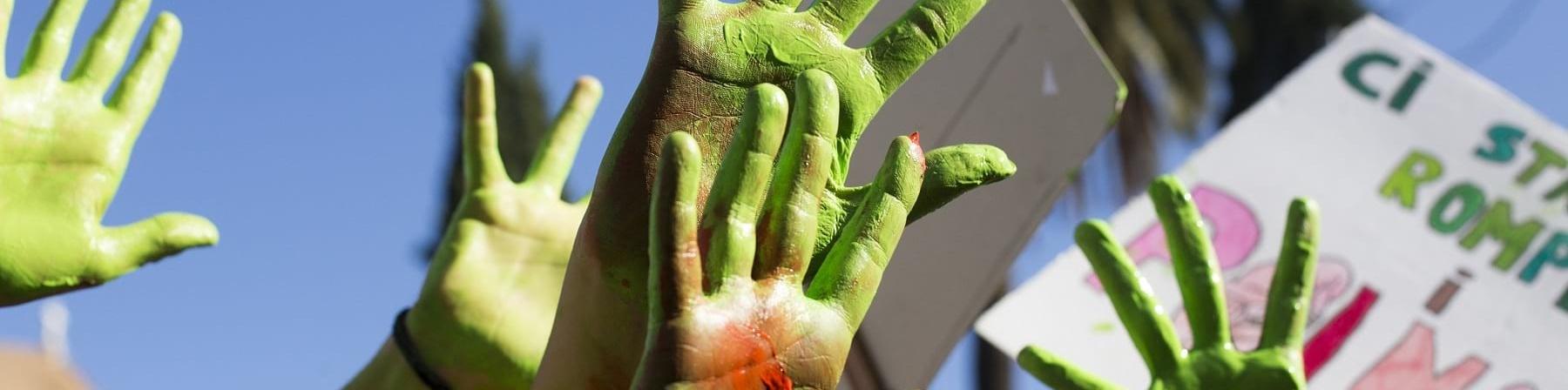 Mani verdi di bambini alzate al cielo con cartelloni