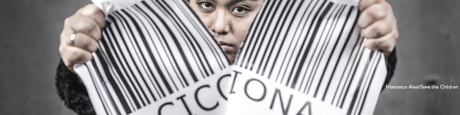 """Una ragazza strappa un grande codice a barre con la scritta """"cicciona"""""""