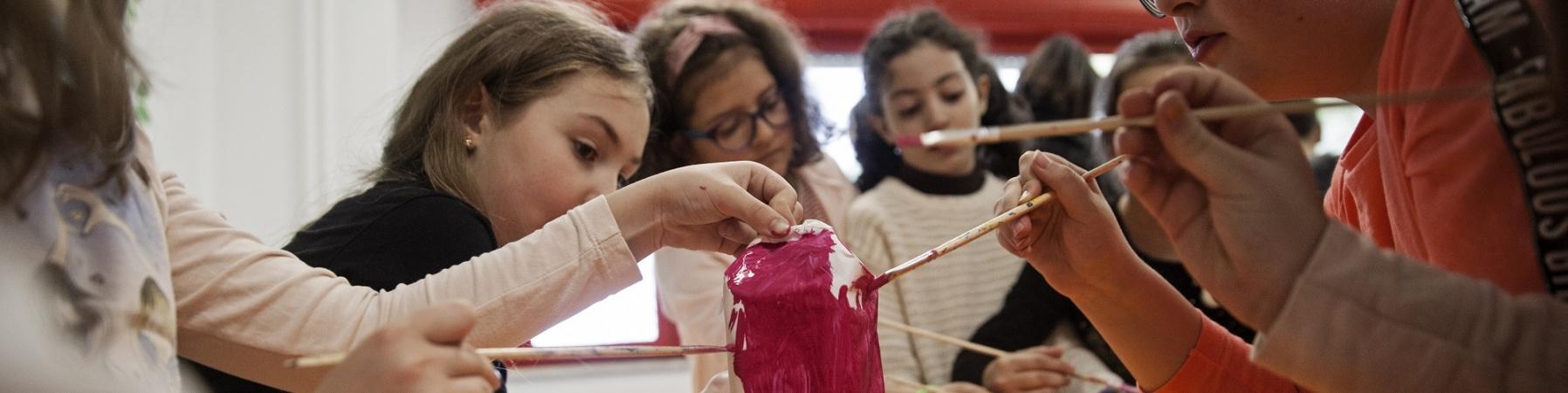 5 ragazze al banco di scuola stanno dipingendo di rosa un loro lavoro artistico