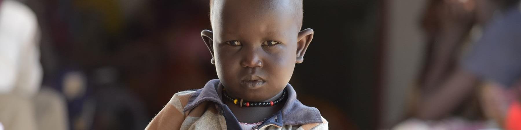 Mezzo busto di un bambino sudanese con maglietta a righe arancioni blu e bianche che tiene con due mani un foglio