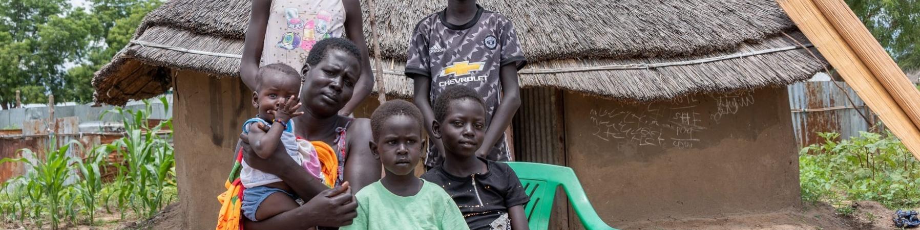 Famiglia sud sudanese in posa davanti alla propria capanna