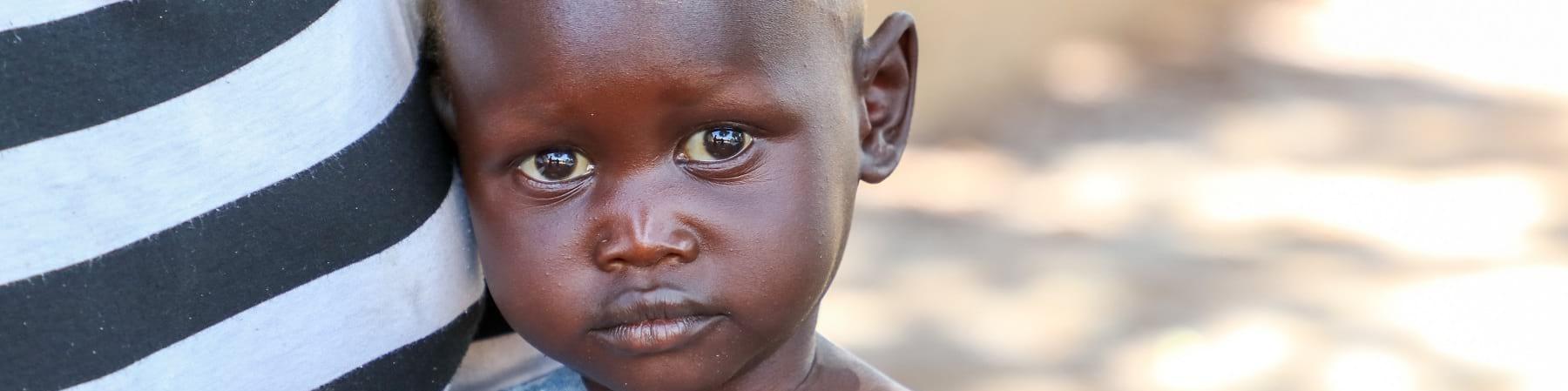 primo piano di un bambino sud sudanese con maglietta grigia è vicino alla pancia di un adulto con maglietta a righe bianche e nere