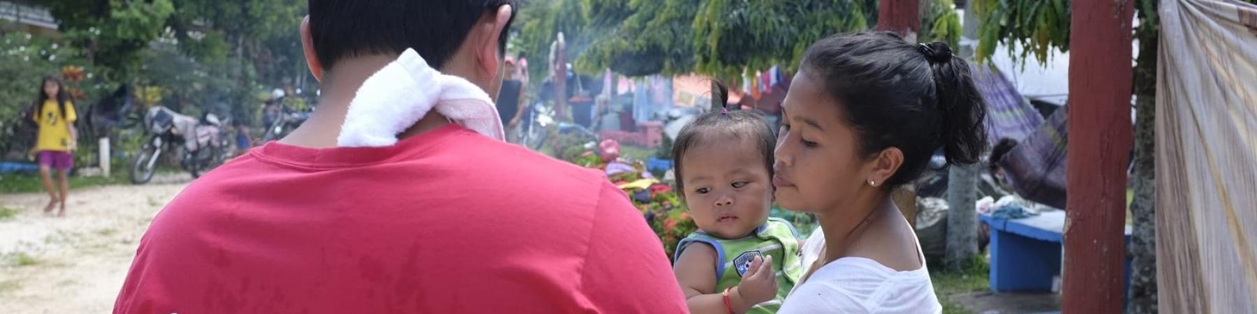 Operatore Save the Children presta assistenza a una mamma filippina con bambino in braccio