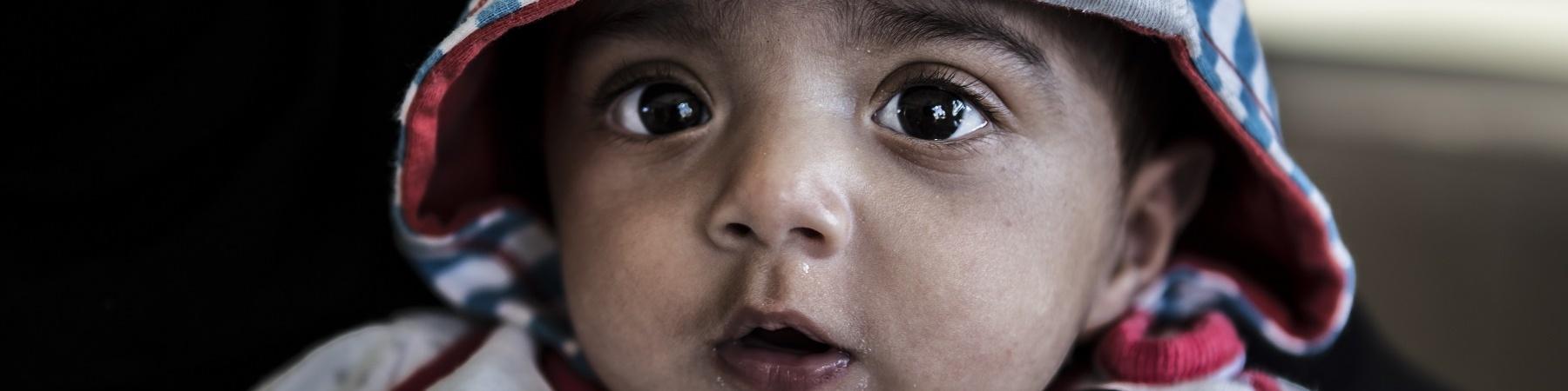 bambino di pochi mesi inquadrato in primo piano con tutina e cappuccio sulla testa