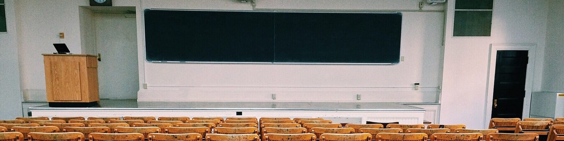 Aula universitaria vuota con sedie di legno pieghevoli, lavagna e leggio su un rialzo.