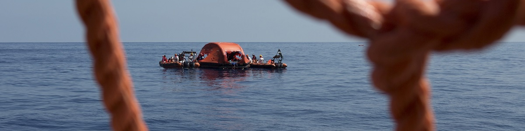 primo piano di una rete rossa di una barca dalla quale si vede il mare e un barchino di salvataggio a pochi metri