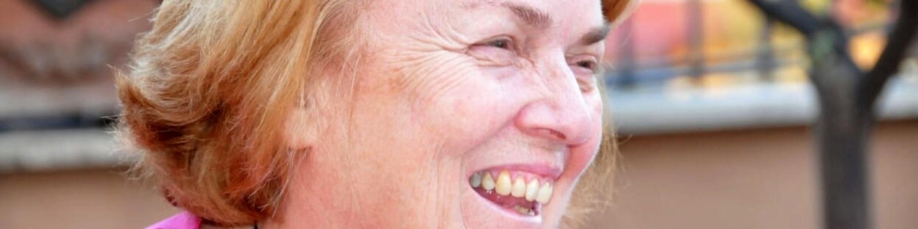 primo piano di una signora bionda sorridente con maglietta rosa