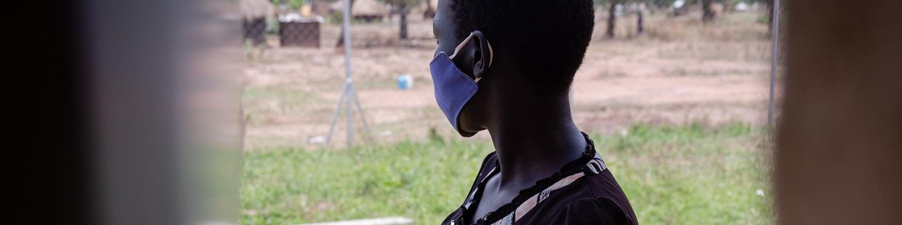 una ragazza ugandese vista attraverso una finestra è girata dall altro lato e guarda un prato verde. La ragazza è incinta e indossa una maglietta nera con motivi floreali.