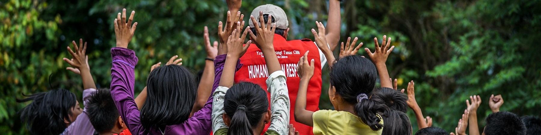 gruppo di bambini e un operatore di spalle con le braccia alzate esultando
