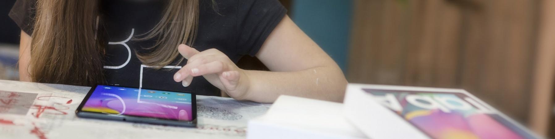 ragazza seduta alla scrivania studia sul suo tablet