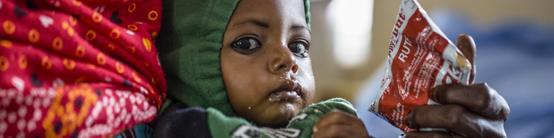 bimbo in braccio alla sua mamma mentre mangia il plumpynut, la pasta di arachidi altamente proteica contro la malnutrizione